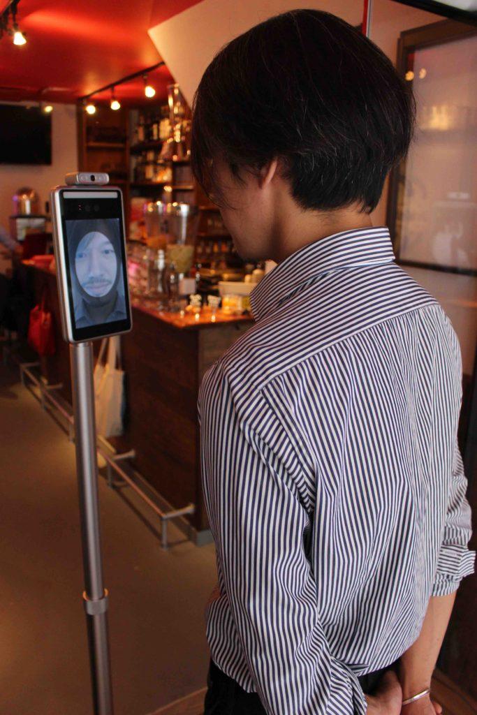 自動検温装置で体温を計測する男性